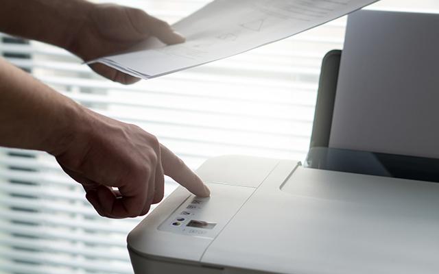 Imprimante avec une main appuyant sur un bouton