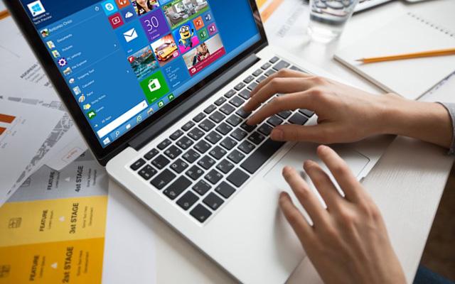 Mains cliquant sur un pc portable avec le bureau Windows 10